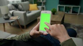 Uomo a casa Sitng su uno strato facendo uso di Smartphone con lo schermo verde del modello archivi video