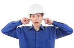 Uomo in casco con le orecchie chiuse Immagine Stock