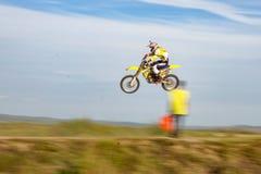 Uomo in casco rosso che guida una motocicletta gialla sulla pista di autunno immagine stock libera da diritti