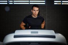 uomo castana bello all'allenamento in palestra che corre velocemente su una pedana mobile Fotografia Stock