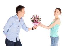 Uomo casuale che dà i fiori all'amica Fotografie Stock