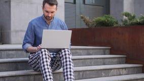Uomo casuale che lavora al computer portatile che si siede sulle scale fuori dell'ufficio stock footage