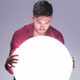 Uomo casuale che legge il suo futuro in una grande palla di luce Fotografie Stock Libere da Diritti