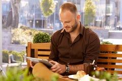 Uomo casuale che per mezzo del computer della compressa Fotografie Stock Libere da Diritti