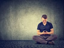 Uomo casuale che per mezzo dello smartphone mentre sedendosi immagini stock