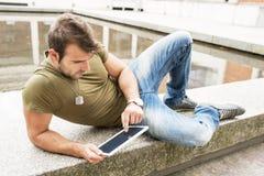 Uomo casuale che si rilassa nella via con il computer della compressa fotografie stock