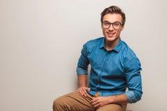 Uomo casuale che si siede e che sorride nello studio con lo spazio della copia Immagine Stock