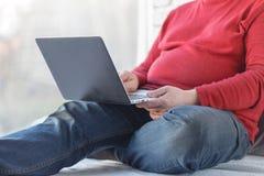 Uomo casuale che si siede e che lavora con il computer portatile sul pavimento di legno Fotografia Stock