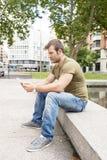 Uomo casuale che si siede nella via e che tiene il computer della compressa fotografie stock