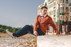 Uomo casuale che si siede sul marciapiede in vecchia città e che guarda asid Immagine Stock