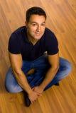 uomo casuale che si siede sul pavimento Fotografia Stock Libera da Diritti