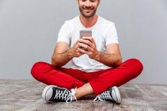 Uomo casuale che si siede sul pavimento e che usando smarpthone Immagini Stock Libere da Diritti