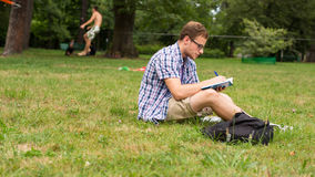 Uomo casuale che studia all'aperto con un taccuino. Fotografie Stock Libere da Diritti