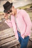 Uomo casuale con il cappello che decolla i suoi occhiali da sole Fotografie Stock