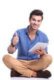 Uomo casuale con il computer del cuscinetto della compressa che fa il segno giusto Immagini Stock Libere da Diritti