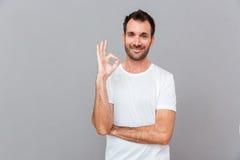 Uomo casuale felice che mostra segno giusto con le dita Immagine Stock