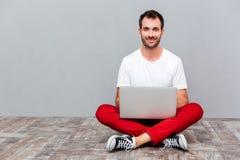 Uomo casuale felice che si siede sul pavimento con il computer portatile Fotografie Stock