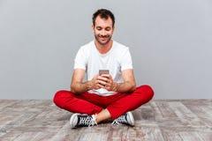 Uomo casuale felice che si siede sul pavimento e che usando smarpthone Immagine Stock