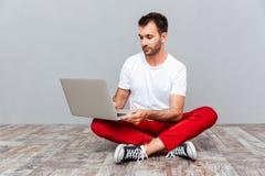 Uomo casuale pensieroso che si siede sul pavimento con il computer portatile Fotografia Stock