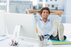 Uomo casuale rilassato con le gambe sullo scrittorio in ufficio luminoso Fotografia Stock