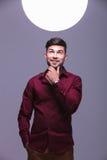 Uomo casuale sorridente che esamina una grande palla di luce Fotografie Stock Libere da Diritti