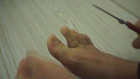 Unghie del piede del taglio dell uomo con le forbici in bagno