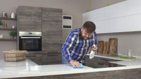 Uomo caucasico allegro spesso con una barba che fa la pulizia nella cucina, lavante il controsoffitto, interno moderno archivi video