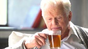 Uomo caucasico anziano che beve un tè delizioso in un appartamento moderno archivi video