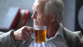 Uomo caucasico anziano che legge un libro e che beve un tè delizioso in un appartamento moderno archivi video