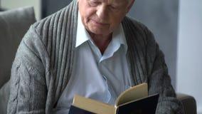 Uomo caucasico anziano che legge un libro in un appartamento moderno stock footage