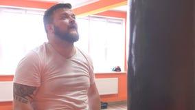 Uomo caucasico bagnato e sudato, barbuto che inscatola un punching ball nell'addestramento alla palestra archivi video