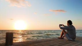 Uomo caucasico che fotografa alba dal molo stock footage
