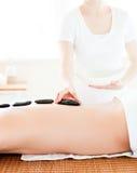 Uomo caucasico che ha un massaggio con le pietre calde Fotografie Stock