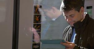 Uomo caucasico che per mezzo del cuscinetto di tocco sul treno stock footage