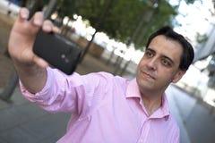 Uomo caucasico che prende autoritratto con il telefono cellulare immagine stock libera da diritti