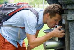 Uomo caucasico che rinfresca alla fontana al parco Fotografia Stock