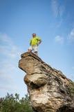 Uomo caucasico che sta sulla punta di alta formazione rocciosa naturale dell'arenaria Fotografie Stock Libere da Diritti