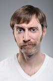 Uomo caucasico con i baffi che Smirking Fotografie Stock