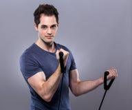 Uomo caucasico con l'allungamento del braccio dall'elastico Fotografia Stock