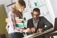 Uomo caucasico e donna che fanno lavoro di ufficio Immagini Stock Libere da Diritti