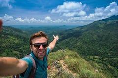 Uomo caucasico sopra la montagna che fa selfie sul fondo di paesaggio grazioso immagini stock libere da diritti