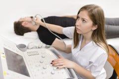 Uomo che è controllato la tiroide al dispositivo di ultrasuono immagini stock libere da diritti