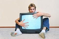Uomo che abbraccia la sua TV Fotografie Stock Libere da Diritti