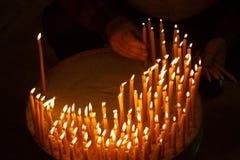 Uomo che accende le candele in una chiesa Fotografia Stock
