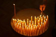 Uomo che accende le candele in una chiesa Immagini Stock