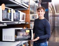 Uomo che acquista forno o girarrosto elettrico fotografia stock libera da diritti