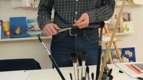 Uomo che affila matita con un grande coltello immagini stock