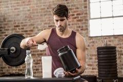 Uomo che aggiunge supplemento dalla latta alla bottiglia fotografia stock