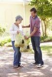 Uomo che aiuta donna senior con acquisto Fotografia Stock Libera da Diritti
