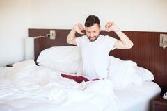 Uomo che allunga e che sbadiglia a letto Fotografia Stock